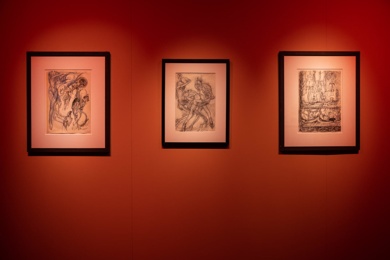 Drei Skizzen von HR Giger hängen an einer rot gestrichenen Wand.