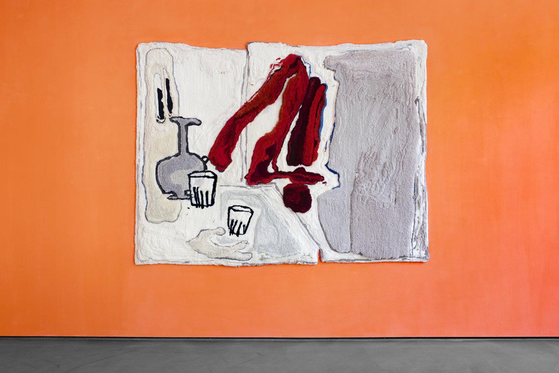 Ein getufteter Teppich von Pia Ferm hängt an einer orangefarben gestrichenen Wand in der Galerie Judith Andreae.