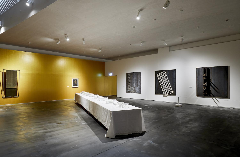Installationsansicht mit Arte Povera Arbeiten unter Anderem von Jannis Kounellis. Eine Wand ist gold gestrichen, im Raum steht ein langes Bankett mit weißer Tischdecke.